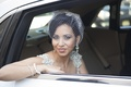 Bride in Inbal Dror dress with rhinestone and pearl straps, birdcage veil, chandelier earrings