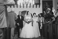 Black and white photo of bride walking down aisle with parents