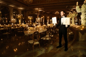 man in tuxedo holding table number signs leading guests to their table wedding ideas