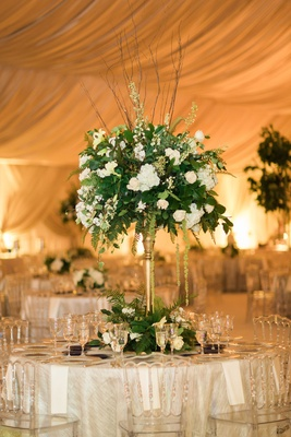 Wedding reception clear chairs tall gold stand with greenery verdure white flowers branches tent