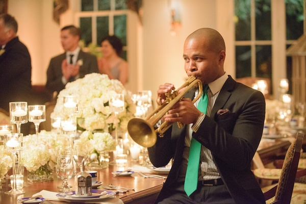 Man playing gold trumpet at dining room table
