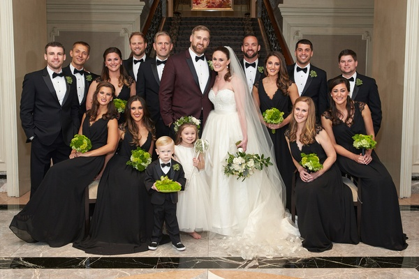 Groom in maroon tuxedo with bride in a line gown and groomsmen in tuxedos bridesmaids in black dress