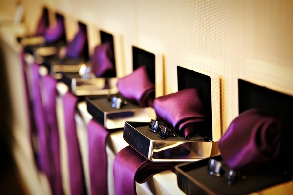 Row of jewelry boxes with purple ribbon and cufflinks