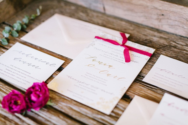 wedding invitation white stationery and gold foil calligraphy text hot pink ribbon bougainvillea