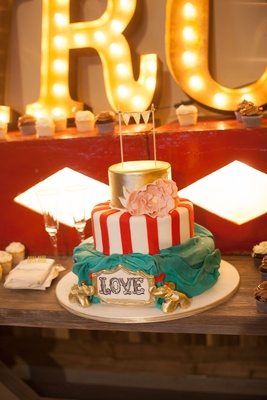 Red and white stripe circus tent cake with gold top tier sugar flower banner gold elephants at base