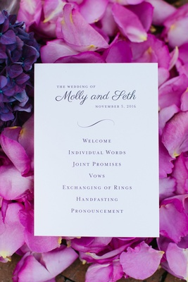 Wedding ceremony program card on bed of purple fuchsia flower petals simple order of events