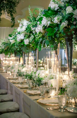 wedding reception head table with tall arrangements of ivy and other greenery