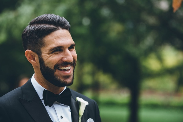 Groom in bow tie and calla lily boutonniere hair cut side part with tuxedo