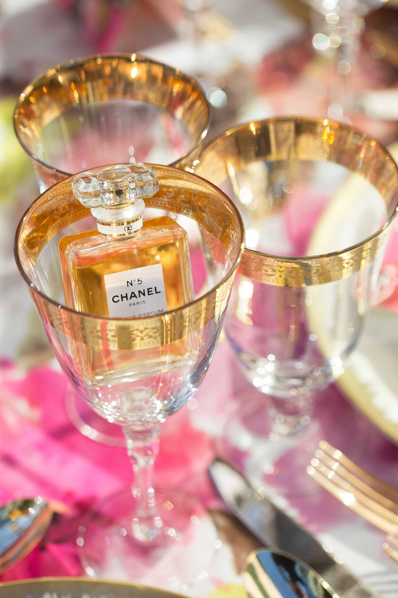 chanel no 5 five perfume inside wine glass with gold details detailing on table with pink linens