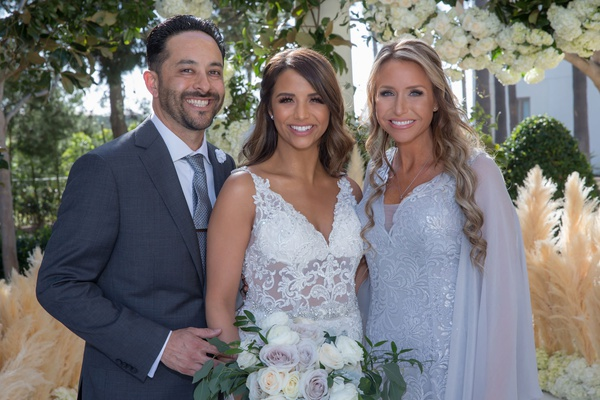 bride in embroidered wedding dress with sheer details with family members in grey silver tones