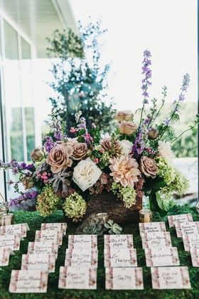 rows of escort cards with floral borders in front of colorful flower arrangement