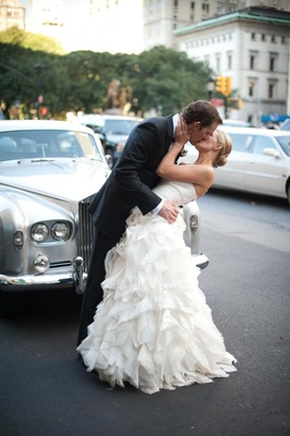Bride and groom kiss in front of classic car in NYC