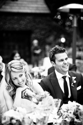 Black and white photo of bride and groom smile at guests during wedding toasts