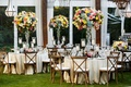 Tent wedding reception private residence tall centerpieces blue pink yellow flowers greenery
