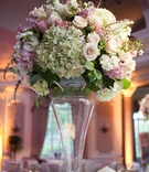 Wedding reception centerpiece of white, green, pink, and light purple flowers in a tall glass vase