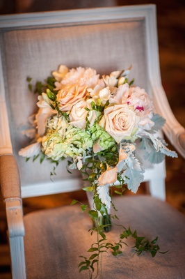 Bride's bouquet of green hydrangeas, peach roses, white peonies with magenta centers, dusty miller