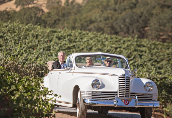 Bride and father of bride being escorted to ceremony space in classic white car convertible