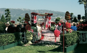 Queen of Hearts themed wedding ceremony with red and green topiaries