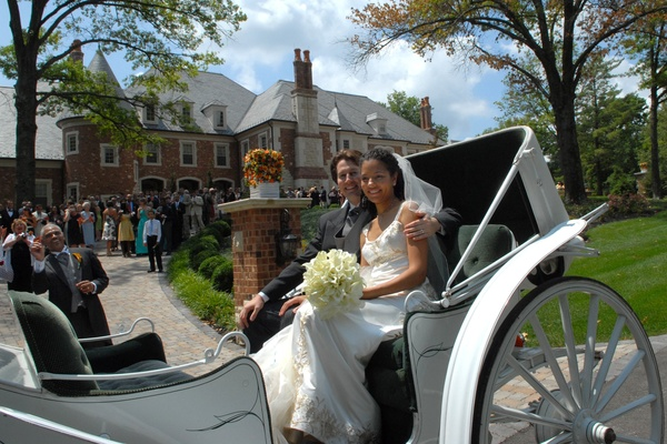 Bride in a Reem Acra gown with groom on a white carriage