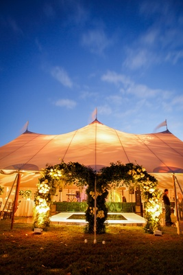 tented reception with arches of greenery and white flowers