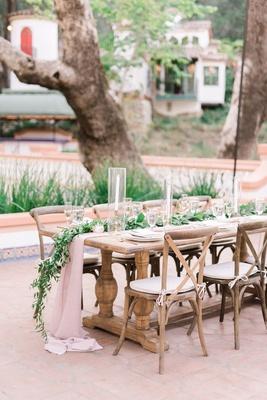 wedding reception outdoor courtyard wood table vineyard chairs blush linens greenery candlesticks