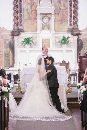 Bride and groom kiss at altar of Catholic wedding church