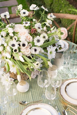 lush floral arrangement with white pink and green on green table linens with white and gold chargers