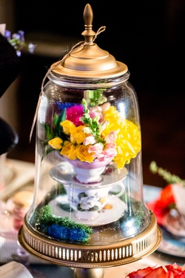 alice in wonderland wedding shoot, stack of teacups with bright flowers under glass dome