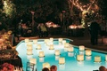 Lily pads topped with paper lanterns on top of pool