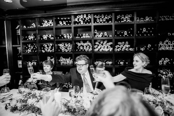 Black & white photo of bride in dark dress, groom in suit with guests at Del Pasto wine cellar