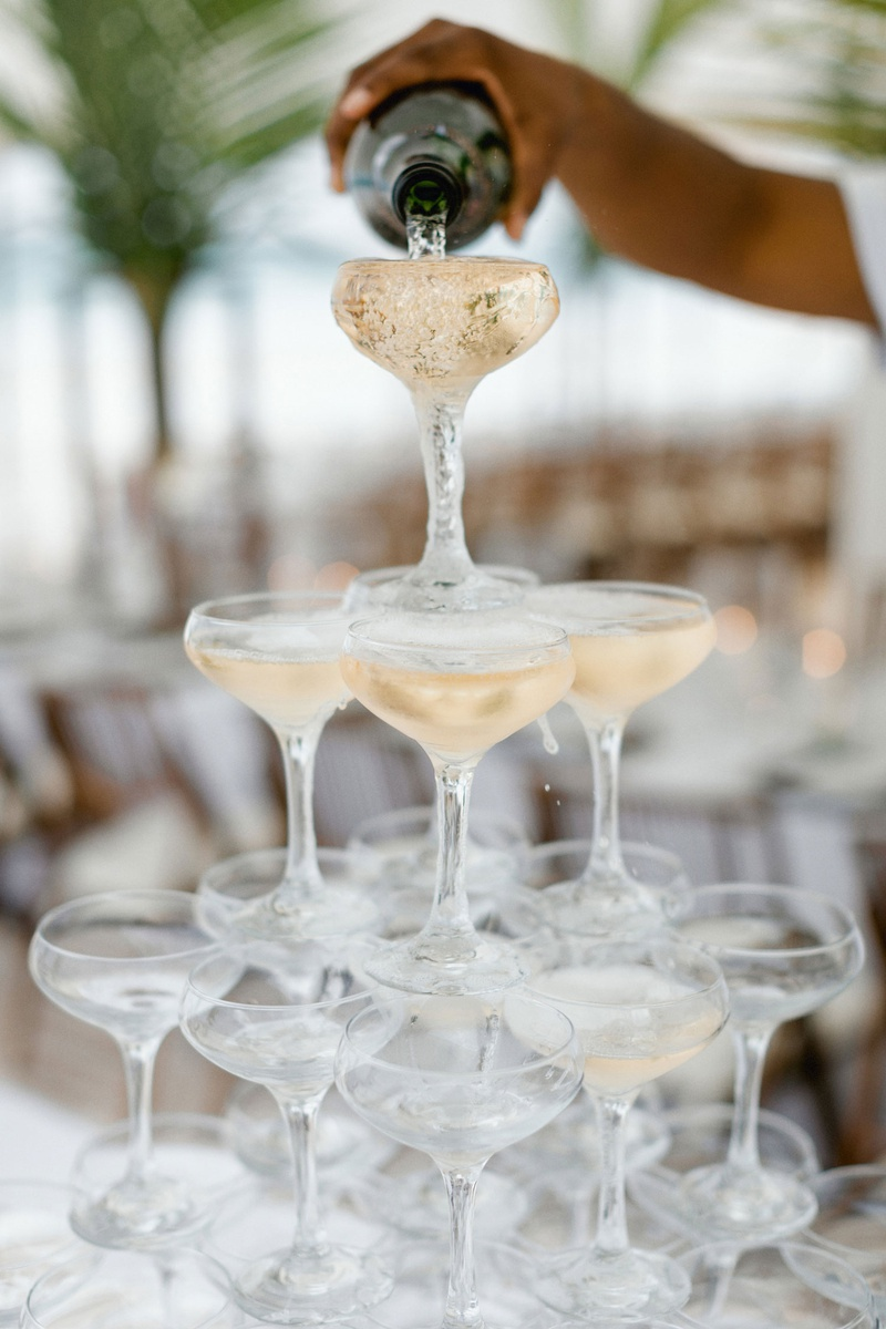 destination wedding in the bahamas champagne coupe glass tower being poured