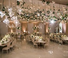 Wedding reception flowers hanging from ceiling chandelier ivory tables serpentine square round ivory