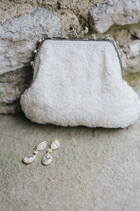 white beaded clutch purse, drop earrings with gold halo