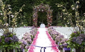 Floral-embellished arch and petal-lined aisle