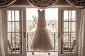 Romona Keveza beaded mermaid wedding dress hangs in window of Grand Del Mar