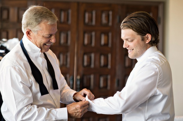 Groom in white button down shirt with father of groom in undone bow tie helping son with cufflinks