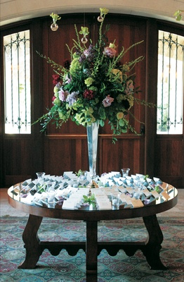 Mirror-top place card table with a large bouquet of red, green, and lavender flowers