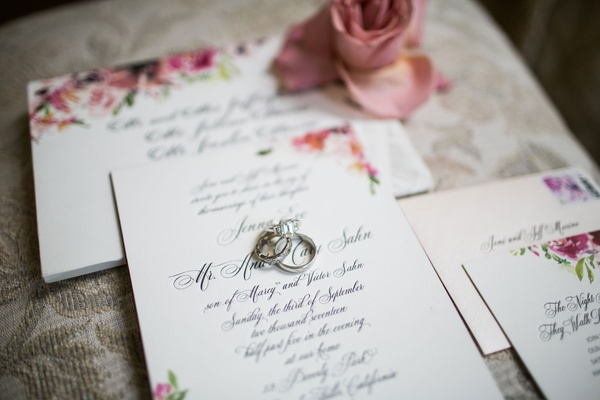 wedding rings on calligraphy invitation suite for wedding pink flowers and stamp