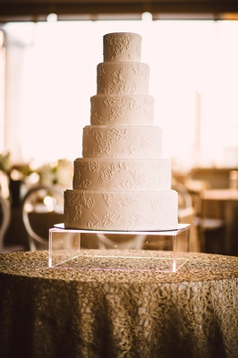 six-tiered wedding cake with lace pattern after bride's dress