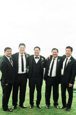 destination wedding hawaii groomsmen groom in vest bow tie groomsmen in black suits ties