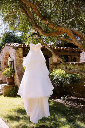 Strapless Hayley Paige wedding dress with tiered skirt hung on tree branch at Hummingbird Nest Ranch