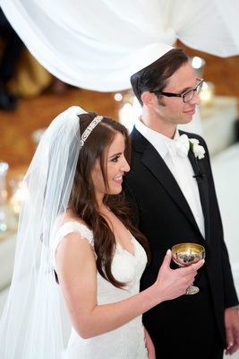 Jewish wedding ceremony bride in Monique Lhuillier wedding dress headband holding kiddush cup