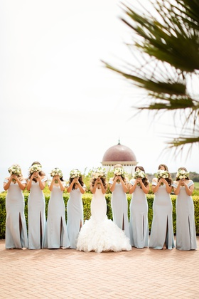 bride in ines di santo, bridesmaids in light blue dessy, bouquets over faces pose