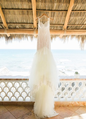 brides white trumpet gown with sweetheart neckline train and straps hangs near beach mexico