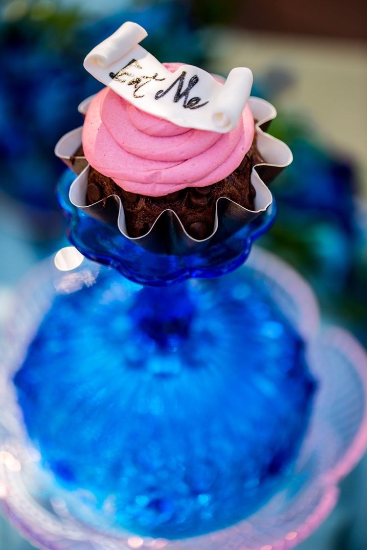 "a miniature chocolate cupcake with pink frosting and ""Eat Me"" on pink base"
