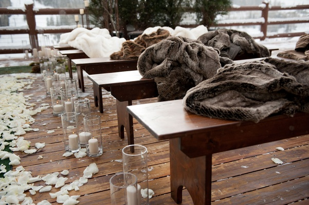 Outdoor winter wedding ceremony with fur blankets on wood benches