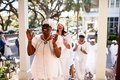 Wedding ceremony entertainment Gullah gospel choir in white outfits singing and clapping in chapel