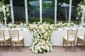 Wedding reception in a glass tent structure head table with large arrangement of white hydrangeas