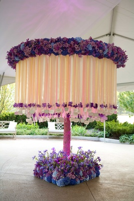 a round floral structure with pink blue and purple flowers hanging by white and off white ribbons