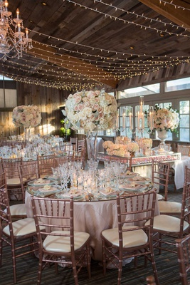 wedding reception ballroom wood ceiling beams string lights tall centerpiece mirror table rose gold
